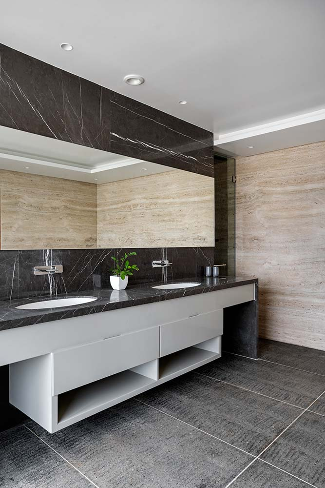 This bathroom has a two-sink vanity and white drawers contrasted by the black marble counter and backsplash.