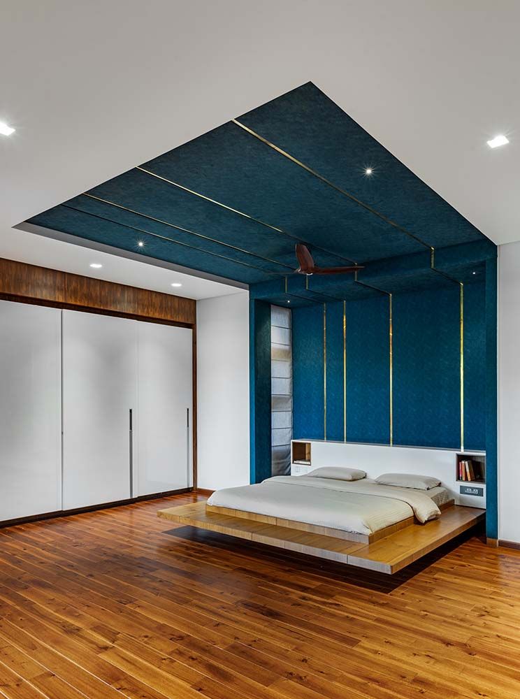 This is a look at the modern floating platform bed complemented by the blue green tone of the wall and ceiling above it the bed.