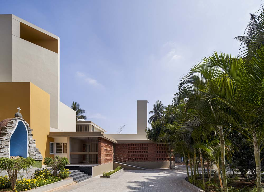 The exterior of the house of worship is paired iwth landscaping of tall tropical trees and concrete walkways.