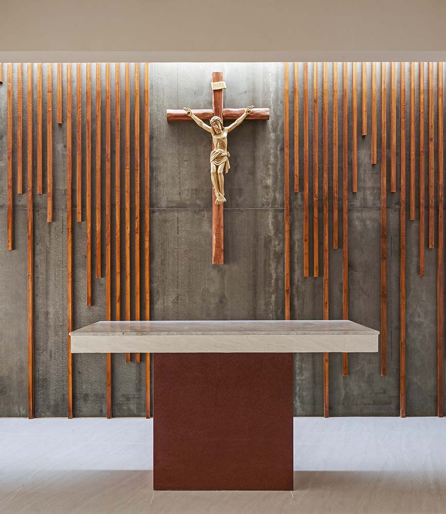 This is a close look at the altar with a crucifix symbol on the far wall across from the altar table with lighting from above.