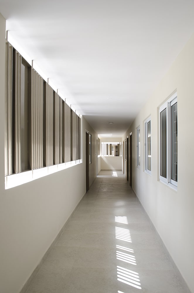 This is a look at the long hallway within the house of worship with bright walls, ceiling and floor brightened by the row of windows.