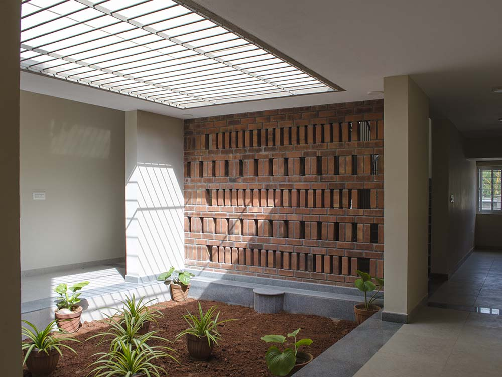 This is a miniature indoor garden within the house of worship with various shrubs topped with a skylight.