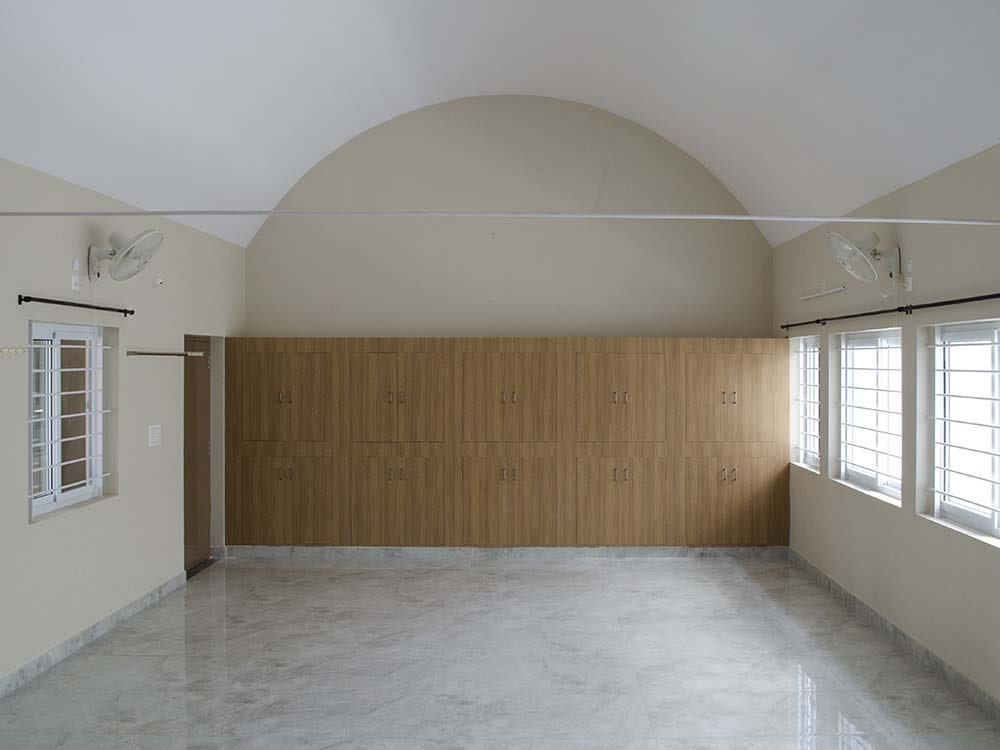 This is a large room within the house of worship with a large wooden wall on the far side topped with an arched ceiling.