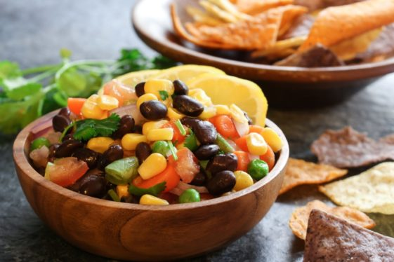 A wooden bowl filled with black bean and corn salsa.