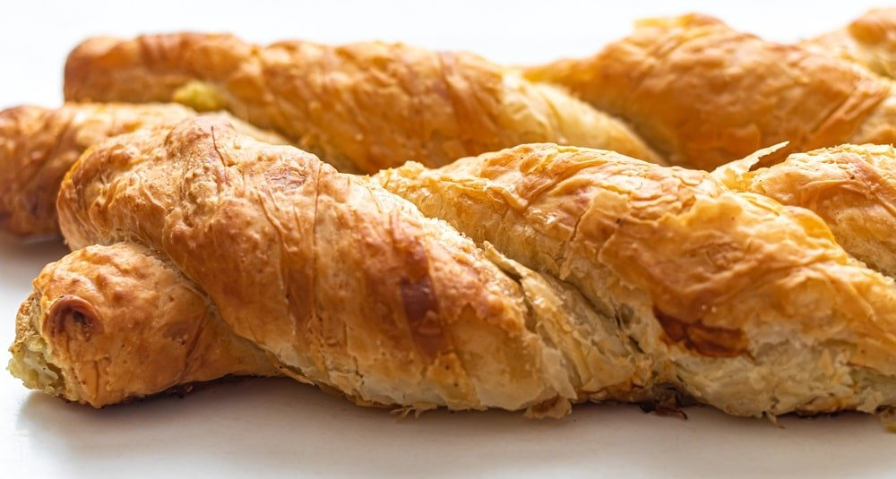 This is a close look at a flaky braided chicken pastry roll.