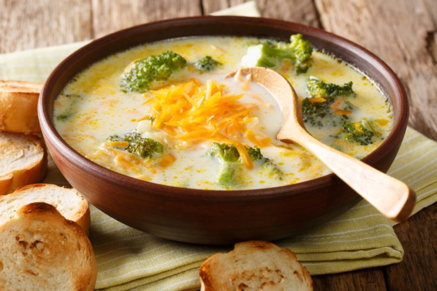 A bowl of broccoli and cheese soup with a side of bread.