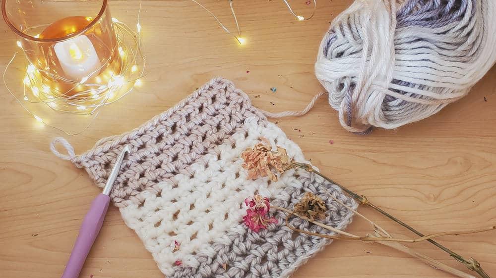 Crochet hooks beside a half-finished bulky yarn project.