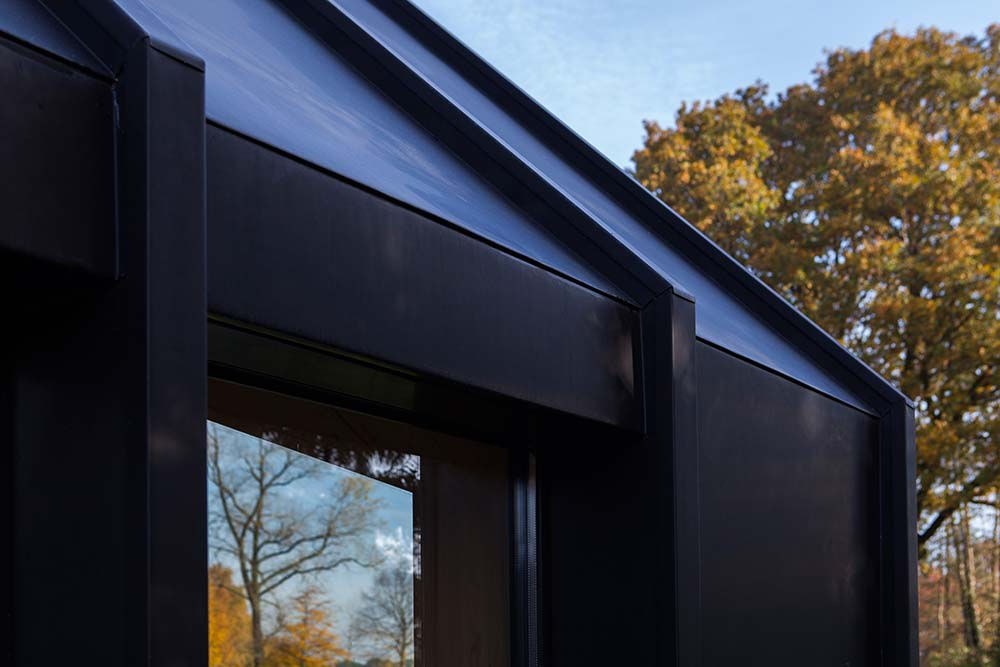This is a close look at the the black exterior wall material of the modern structure and its glass window.
