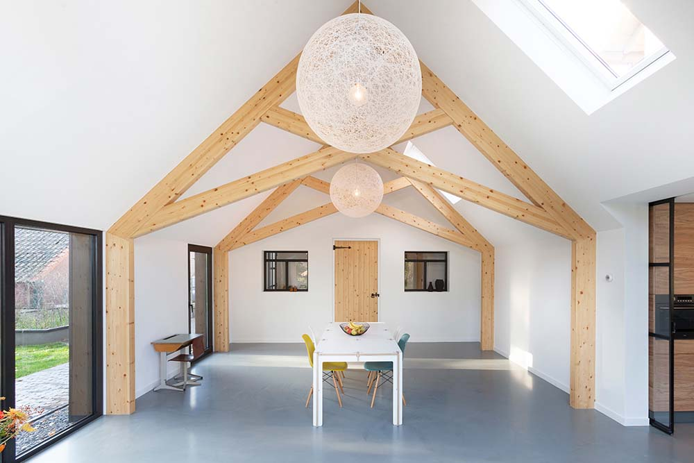 The tall cathedral white ceiling with exposed wooden beams also have spherical pendant lights.