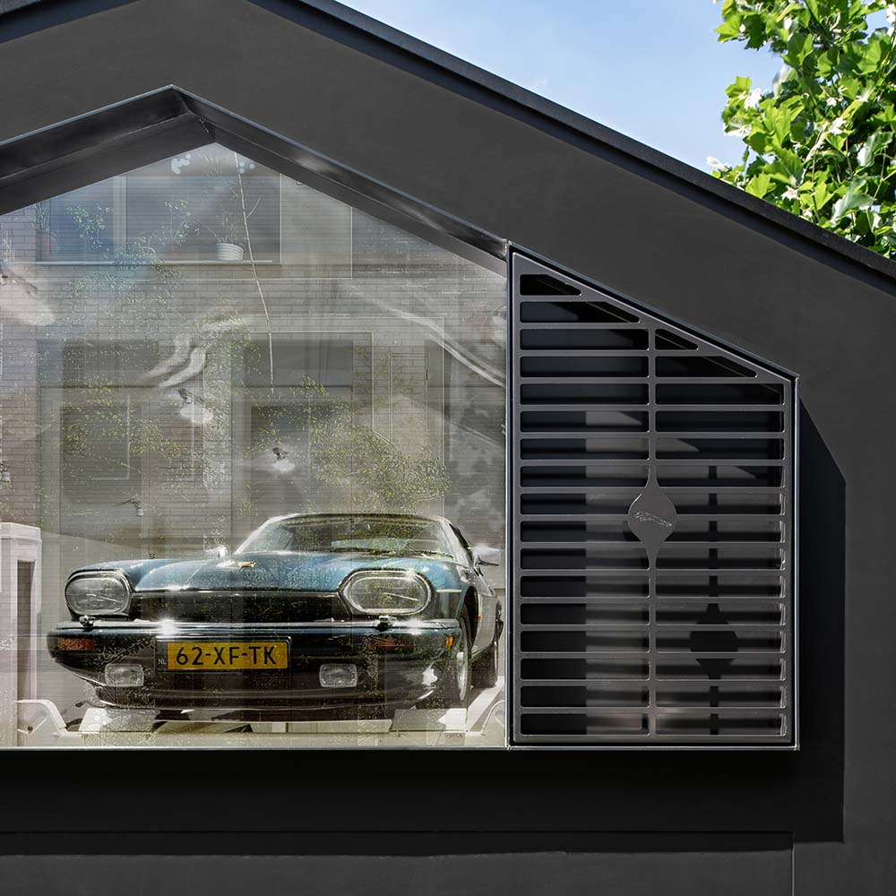 This is a close look at the house's garage with a glass wall and a car inside.