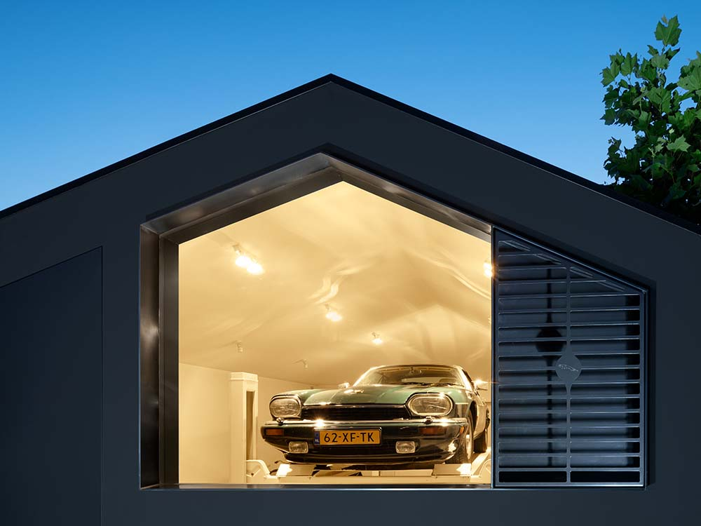 This is a nighttime view of the garage that has a warm yellow from its interior lights escaping through the glass wall.