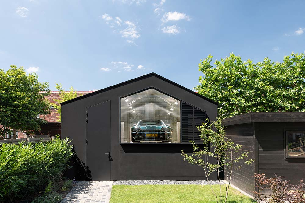 This is a view of the garage adorned with a grass lawn and a concrete walkway lined with shrubs on the side.