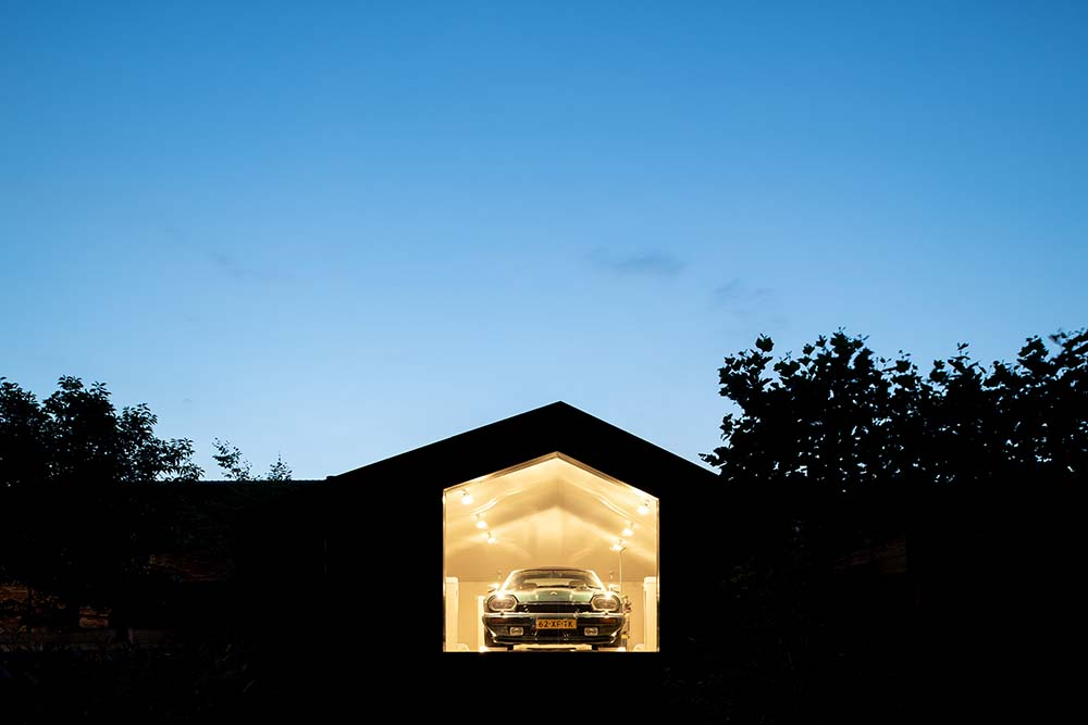 This is a nighttime view of the garage showcasing the warm glow of the interior that escapes through the glass wall.