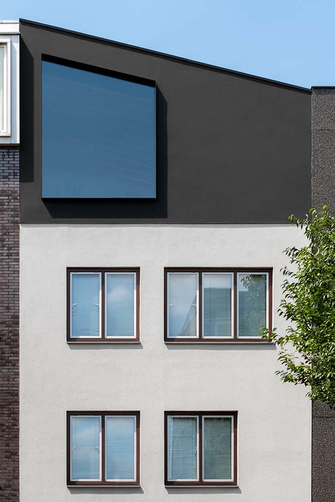 This is a close look at the upper floors of the front of the house with a modern design to its white and dark gray façade.