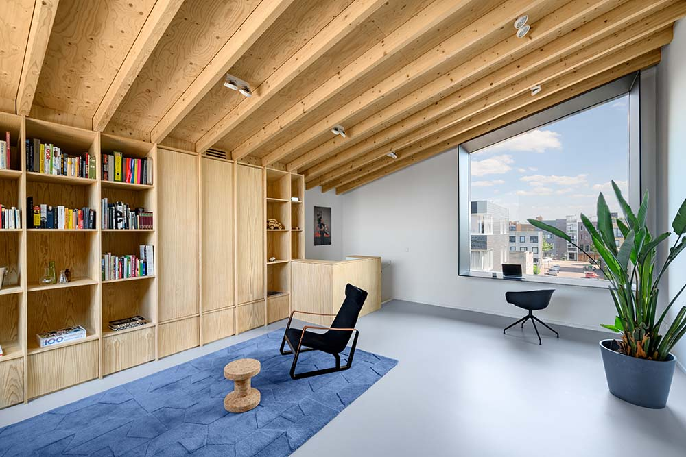 The built-in wooden structure of the bookshelves blend well with the exposed beams of the low shed ceiling.