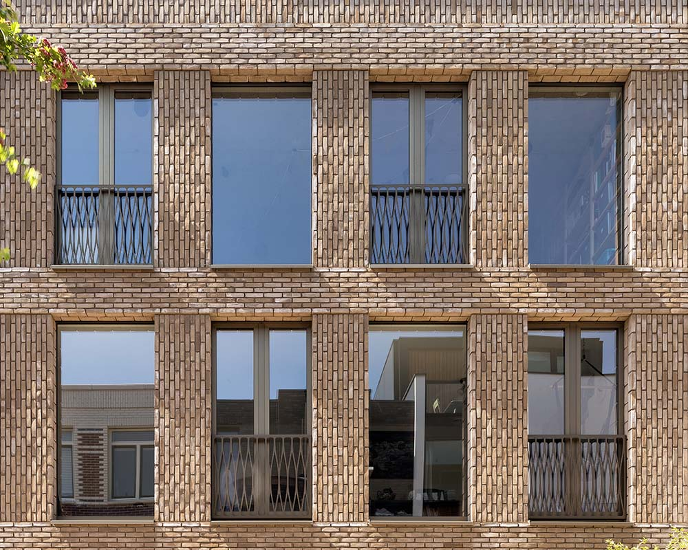 This is a close look at the upper floors of the house with terracotta bricks and glass windows.
