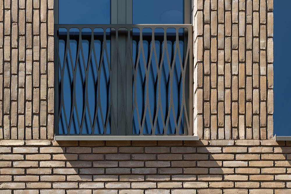 This is a closer look at the terracotta brick exterior wall of the house that pairs well with the glass windows and their wrought-iron railings.