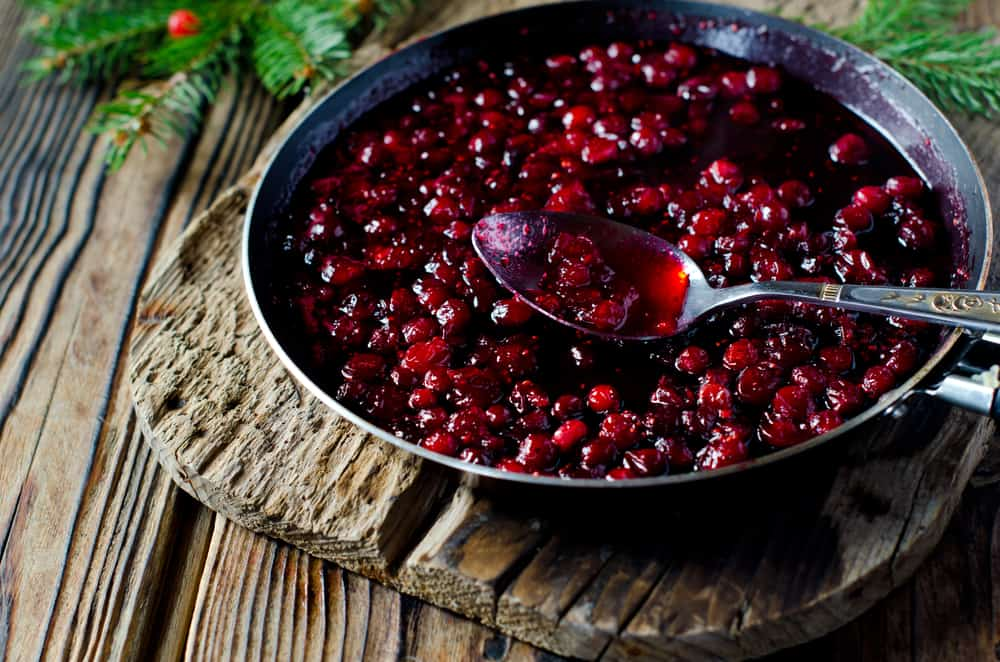 A dish with fresh cherry cranberry sauce on a wooden table.
