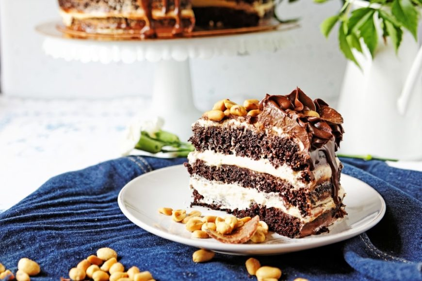 A slice of chocolate lush on a small white plate with toppings of nuts.