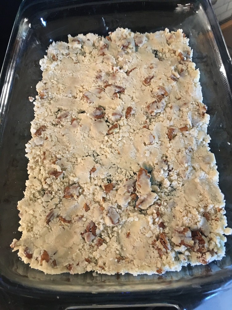 The mixture is then compacted into the bottom layer of the baking pan.