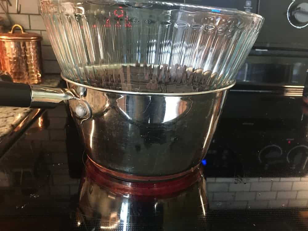 A glass mixing bowl on top of a small pot of hot water.