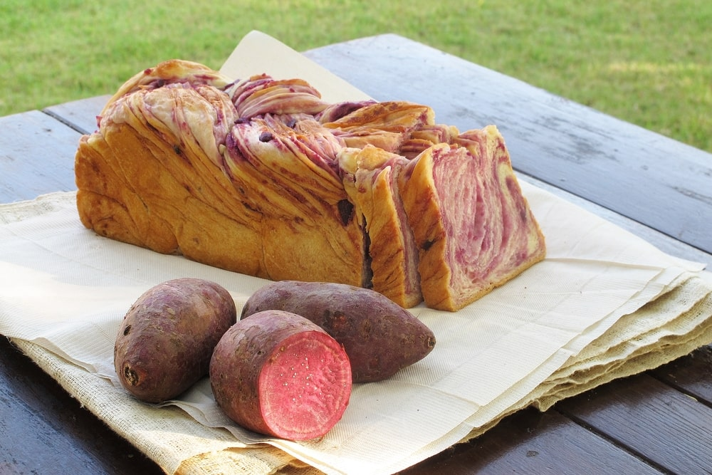 A sliced loaf of cinnamon sweet potato bread with fresh sweet potatoes on the side.