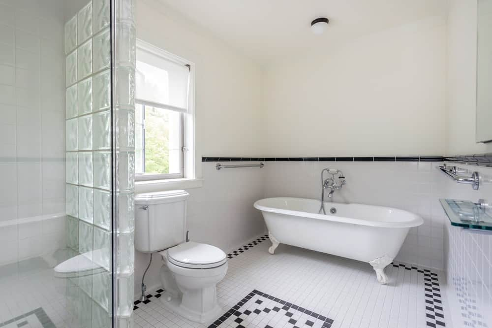 This is a closer look at the bathroom with a freestanding white bathtub at the corner with matching white backsplash. The white elements are accented with black tiles that form patterns on the floor.