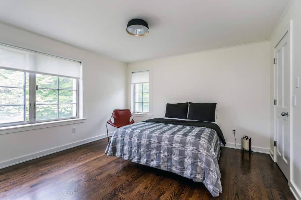 The black flush-mount ceiling light matches the tone of the bed. On the side is a simple chair for a simple reading nook. This is complemented by the hardwood flooring and large windows.