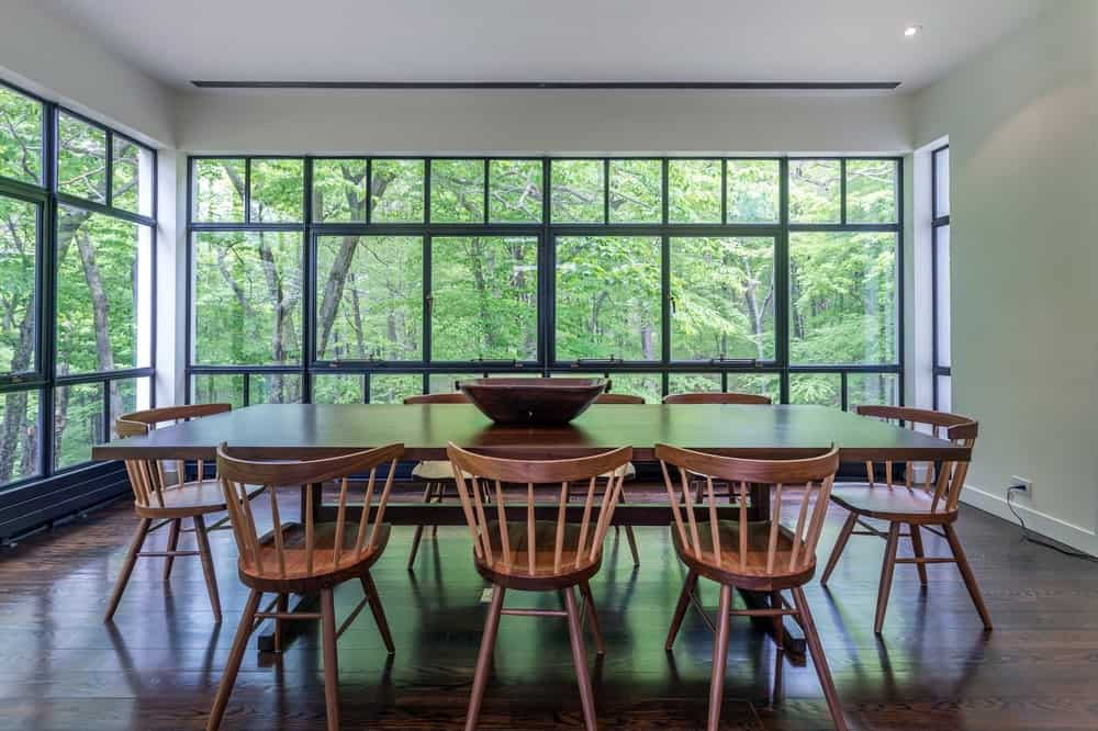 This is a close look at the dining room with a long rectangular wooden dining table surrounded by wooden chairs that stand out against the darker shade of the hardwood flooring.