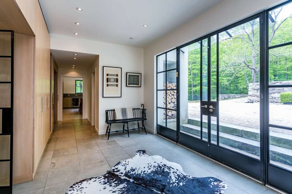 This is a close look at the minimalist foyer upon entry of the house through the glass doors. It has an animal area rug in the middle and a simple bench on the side.