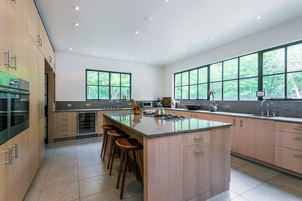 The kitchen has a large kitchen island in the middle of the tiled floor. On one side of the kitchen island is a large wooden structure that houses wooden cabinets and the embedded appliances.