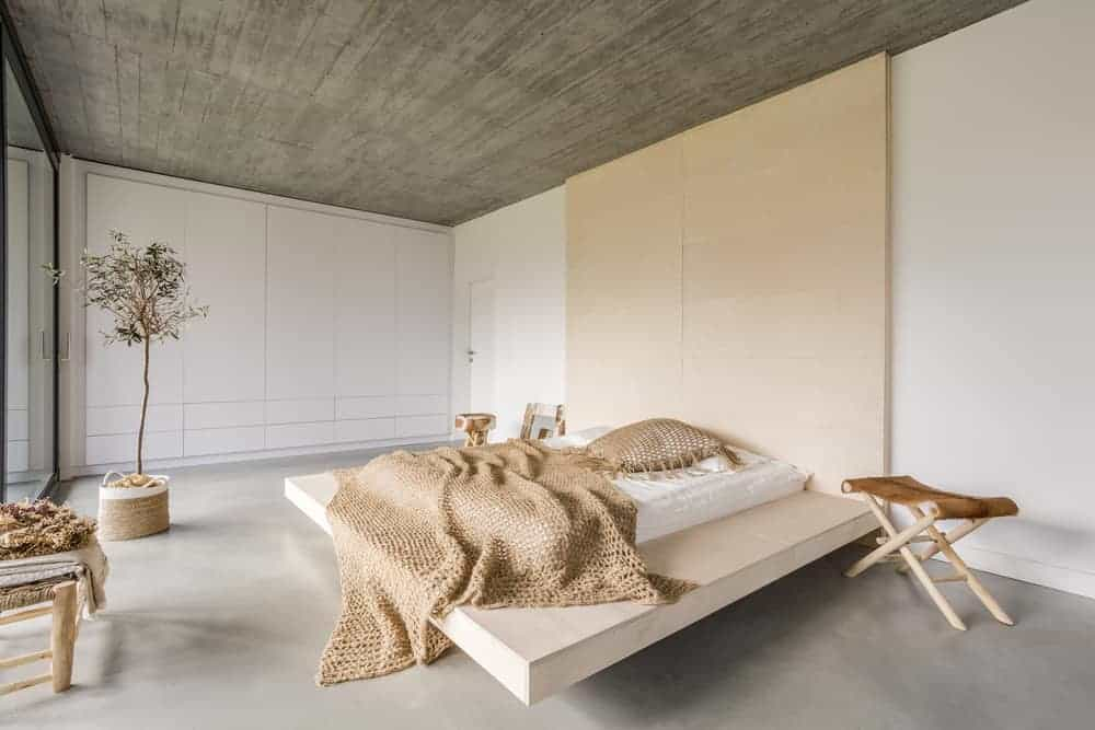 This is a close look at a cozy minimalist style bedroom with a wooden platform bed that extends to its large headboard topped with a concrete ceiling.