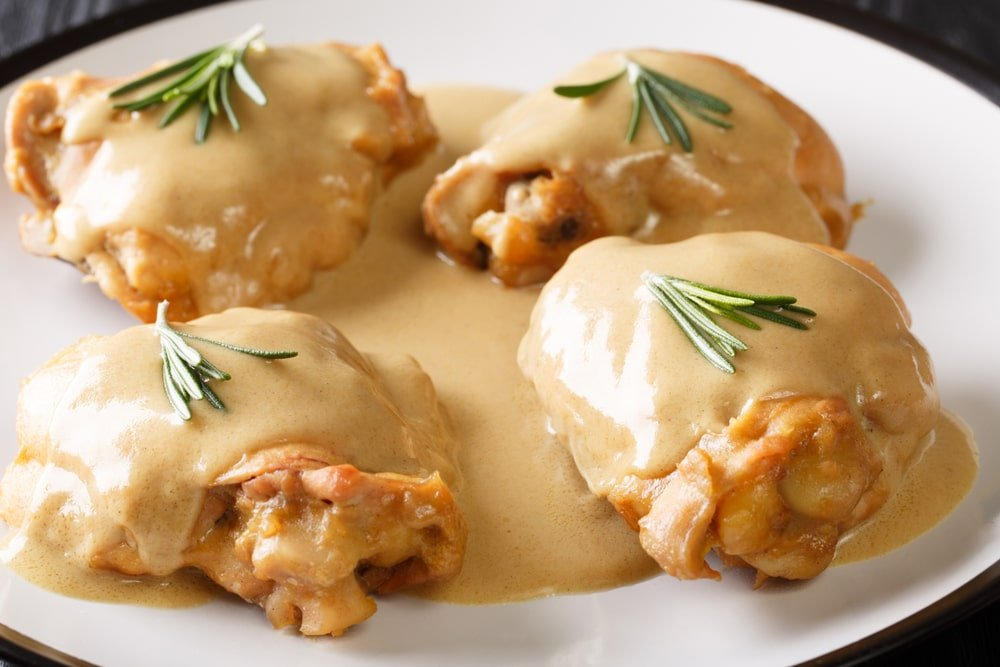 A plate of creamy dijon chicken with herbs on top.