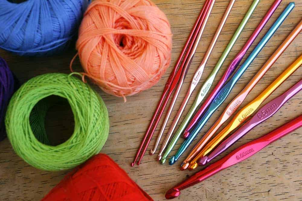 Multicolored crochet hooks beside multicolored balls of yarns.