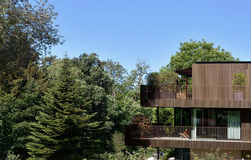 This is an aerial view of the corner of the house with dark brown wooden structures complemented by the tall trees.