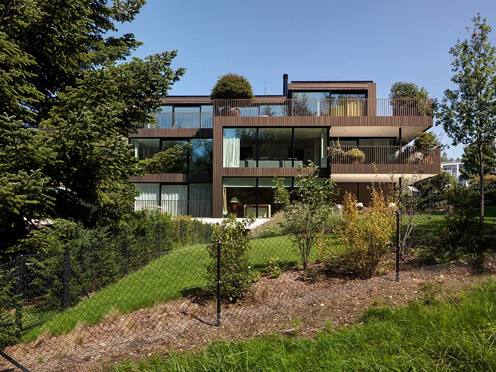 This side of the house exterior has more glass walls and windows to maximize the view of the landscape beyond and let in natural light.