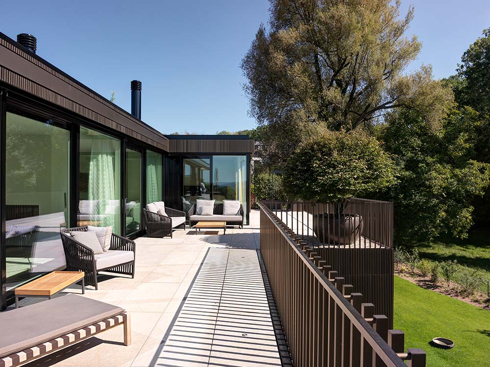This is a close look at the house's terrace balcony with dark brown metal railings to match the dark brown exterior walls fitted with various lounge areas.