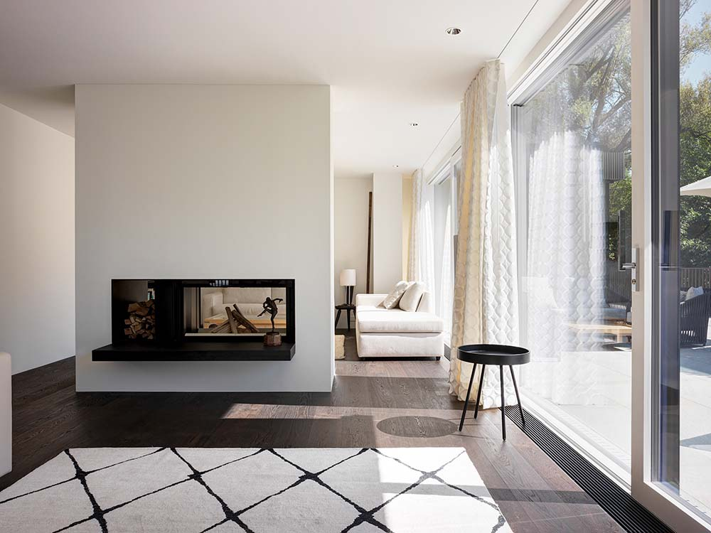 This is a look at the living room that has a modern two-way fireplace and a set of beige sectional sofa.