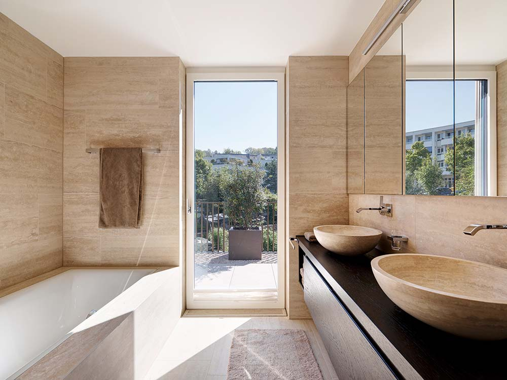 This is the bathroom with a glass door, a two sink vanity and a bathtub across from it.