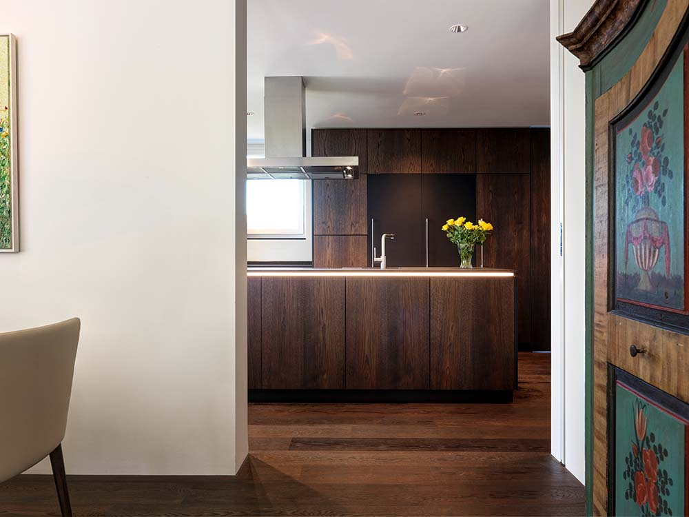 This is a look at the kitchen from the entryway. It has a dark wooden tone on its cabinetry and island that matches well with the hardwood flooring.