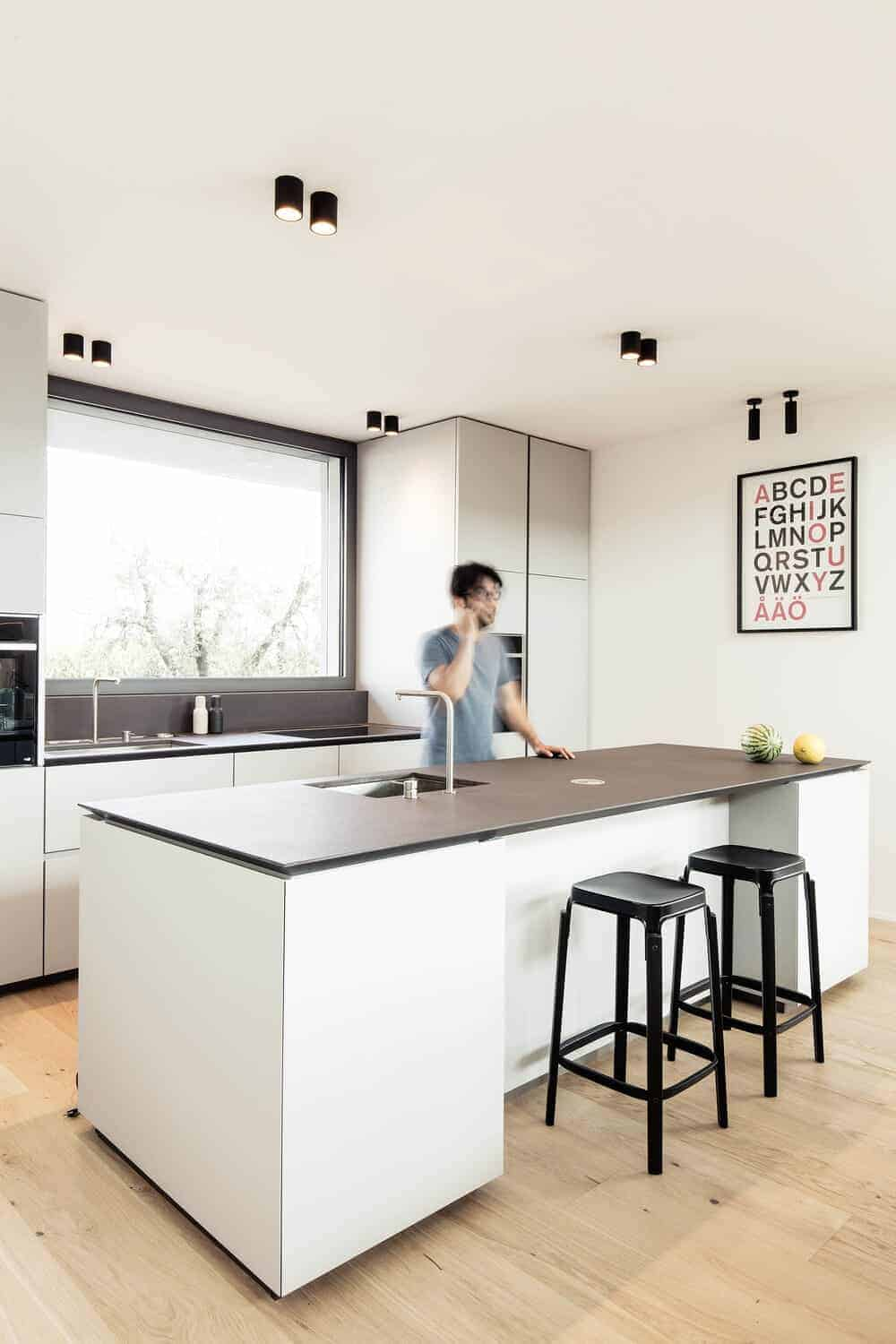 This is a minimalist kitchen with bright white cabinetry that matches with the walls and the kitchen island contrasted by the countertops and modern lighting.