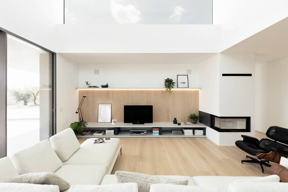 This is a close look at the living room with a large white L-shaped sectional sofa that matches the wall and the modern fireplace beside the large entertainment structure that matches the hardwood flooring.