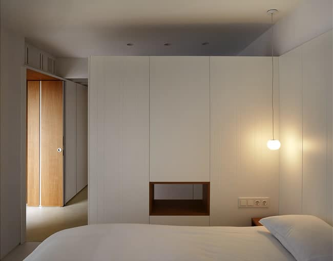 This is a simple minimalist bed with white cabinets and walls to match the white bed. These are then complemented by the warm lighting of the bedside table.