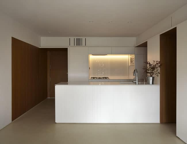 This is a full view of the kitchen that has a large white kitchen peninsula across from the white modern cabinetry that houses the cooking area with its own alcove on the far wall.