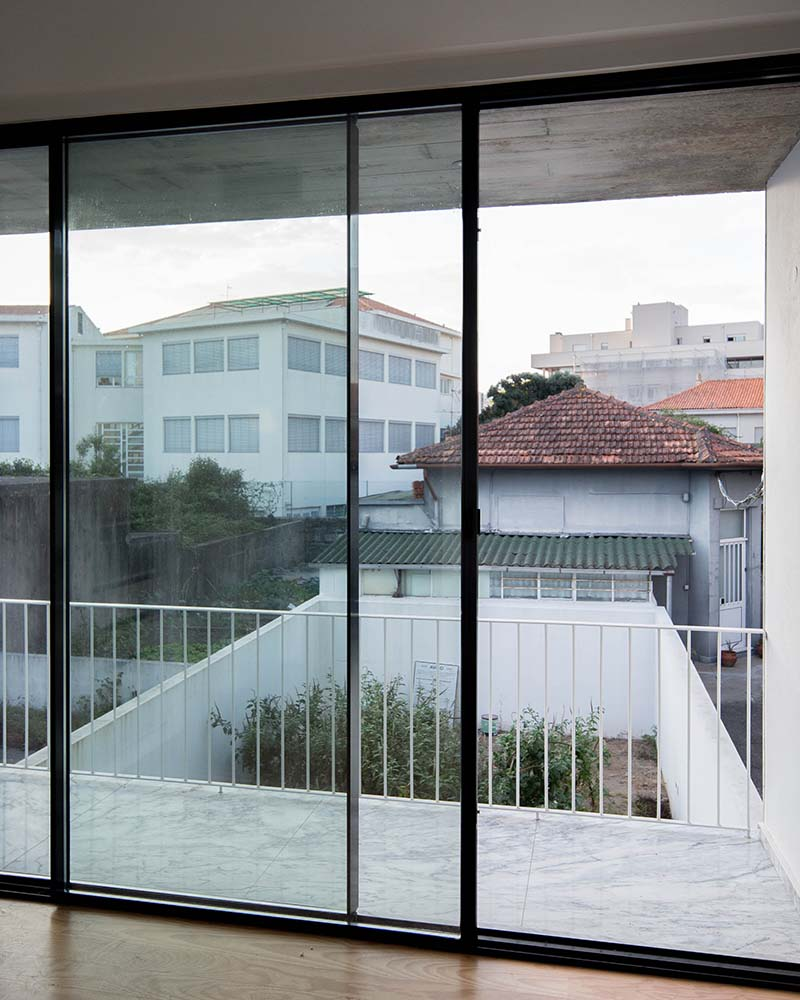 This is a close look at the upper level glass sliding door that leads to the balcony that has white railings and a view of the backyard garden.