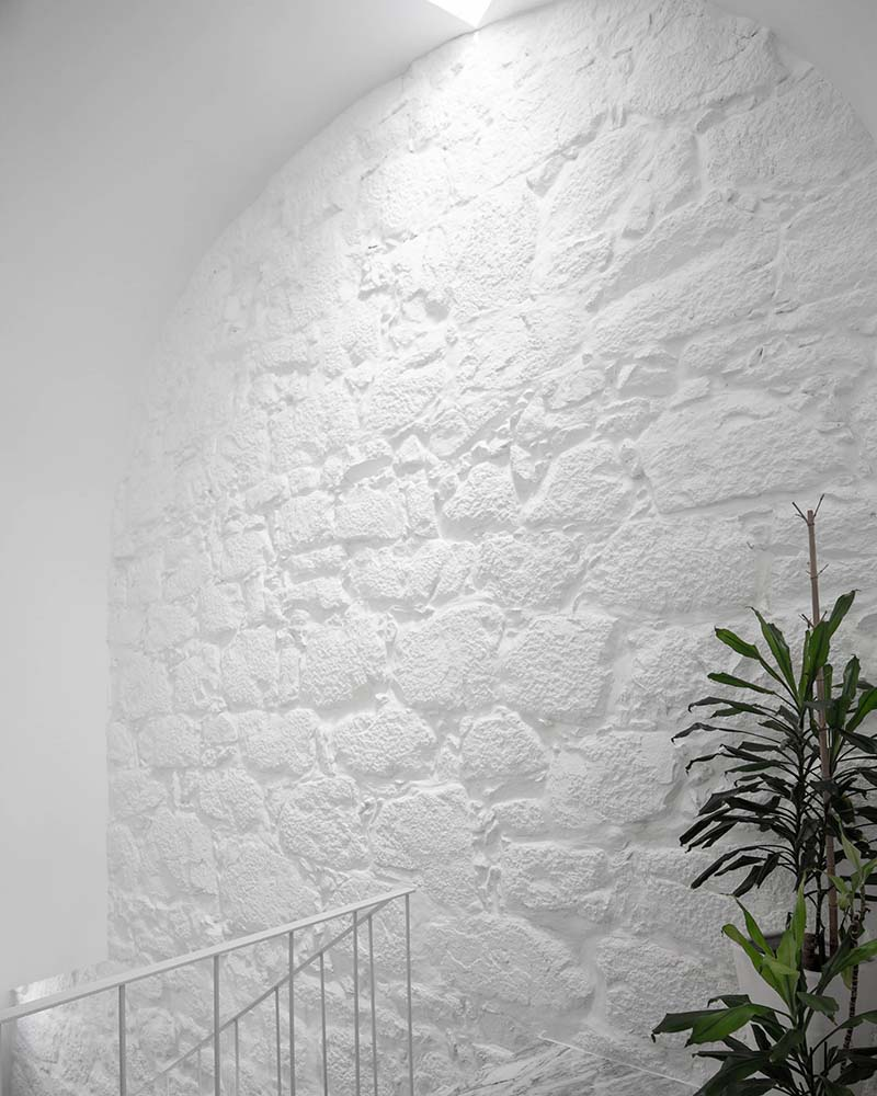 This is a close look at the wall on the side of the upper level landing that has a textured white tone with a potted plant on the side.