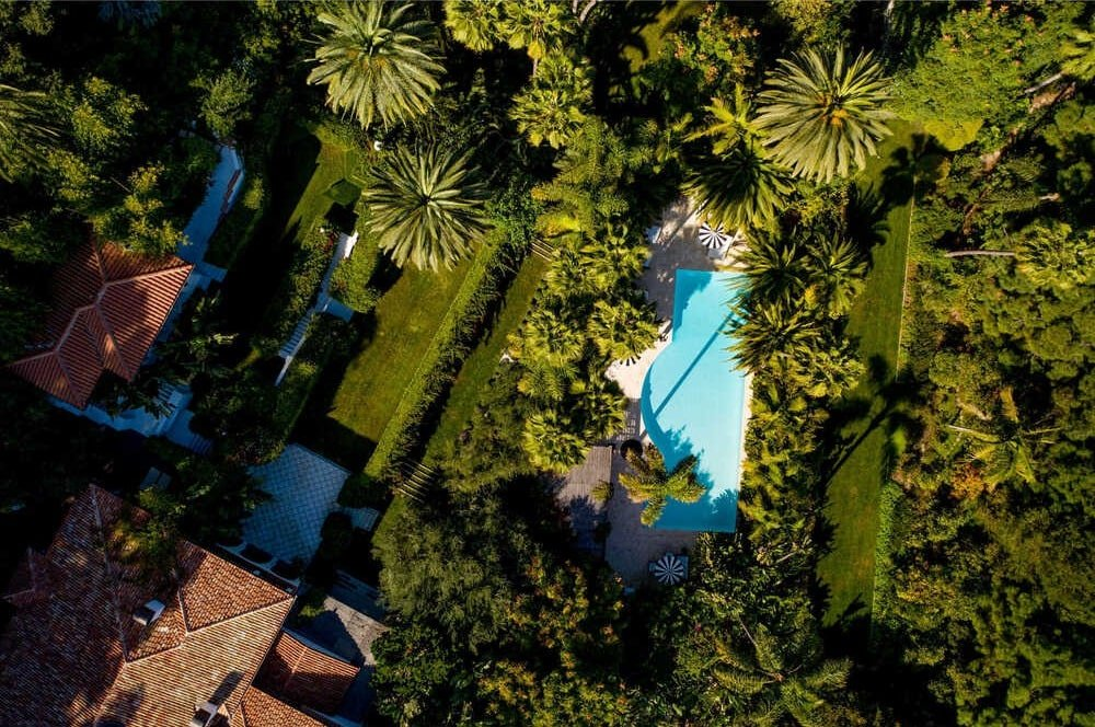 This is an aerial view of the property showcasing the large swimming pool surrounded by the thick landscape of shrubs and trees. Image courtesy of Toptenrealestatedeals.com.