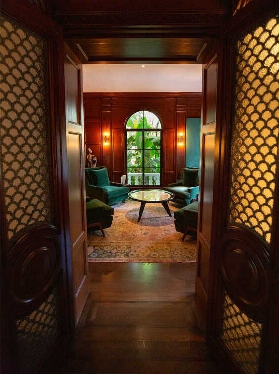 This is a look at the wood-paneled den from the vantage of the double wooden doors of the entrance. Image courtesy of Toptenrealestatedeals.com.