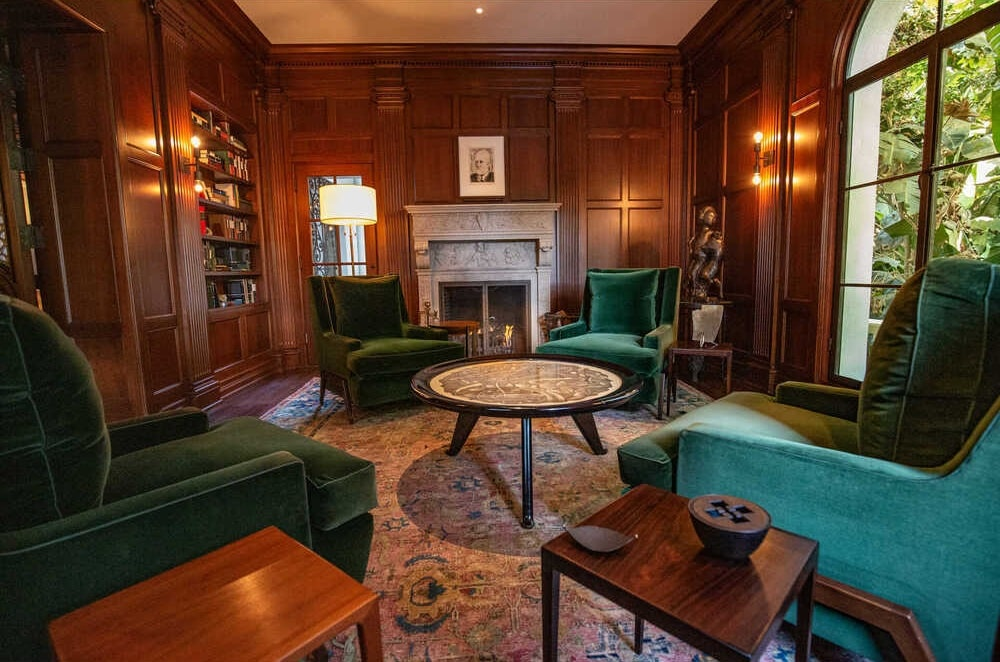 This is a close look at the wood-paneled den with green velvet armchairs surrounding a circular coffee table in the middle of a patterned area rug. Image courtesy of Toptenrealestatedeals.com.