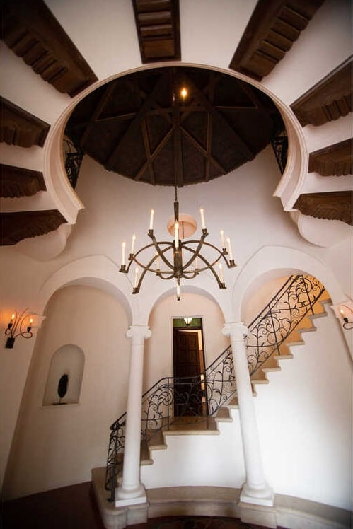 This is a look at the two-story foyer of the main house that has arches, pillars, a staircase on the sides and a large chandelier hanging from a tall ceiling. Image courtesy of Toptenrealestatedeals.com.